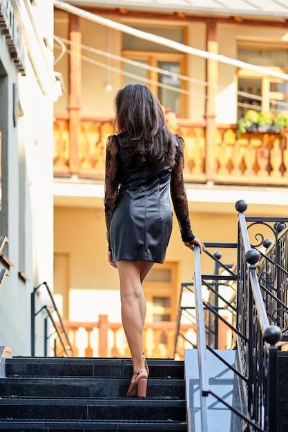 Hintere ansicht der dame im kurzen lederkleid auf der treppe Premium Fotos