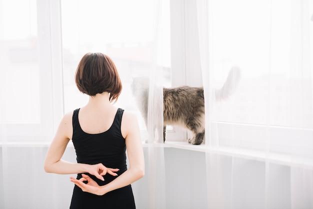 Hintere ansicht der frau die katze betrachtend, die gyan mudra geste in ihr zurück macht Kostenlose Fotos