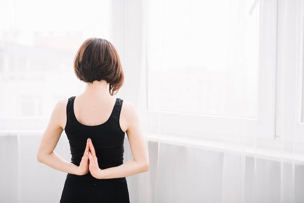 Hintere ansicht der frau ihre hand während des yoga ausdehnend Kostenlose Fotos