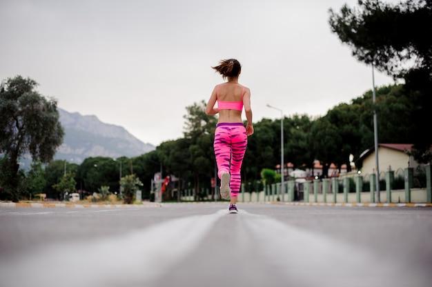 Hintere ansicht der frau morgens laufend entlang die landstraße Premium Fotos