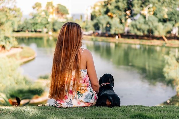 Hintere ansicht der frau und des dachshunds, die nahe dem teich sitzen Kostenlose Fotos