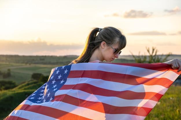 Hintere ansicht der glücklichen jungen frau, die mit usa-nationalflagge im freien bei sonnenuntergang aufwirft. positives mädchen, das unabhängigkeitstag der vereinigten staaten feiert. konzept des internationalen tages der demokratie. Premium Fotos