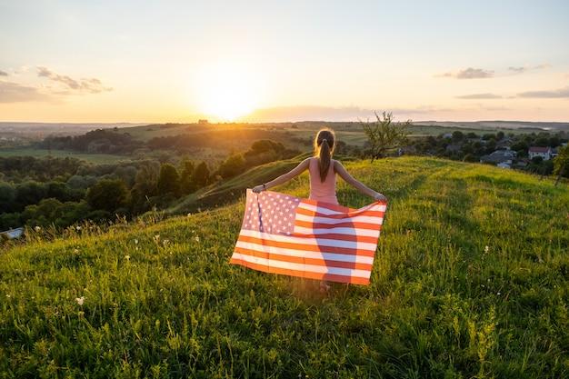 Hintere ansicht der glücklichen jungen frau, die mit usa-nationalflagge steht, die draußen bei sonnenuntergang steht. positives mädchen, das den unabhängigkeitstag der vereinigten staaten feiert. konzept des internationalen tages der demokratie. Premium Fotos