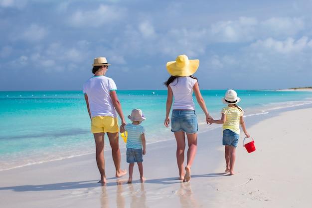 Hintere ansicht der jungen familie mit zwei kindern auf karibischen ferien Premium Fotos