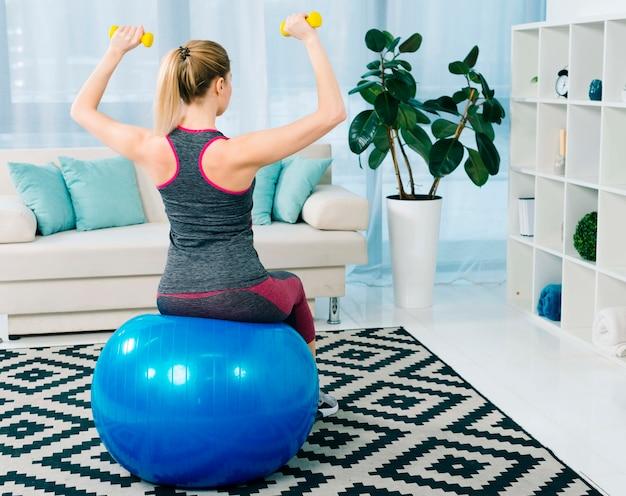 Hintere ansicht der jungen frau der eignung, die auf dem blauen pilates ball trainiert mit gelben dummköpfen sitzt Kostenlose Fotos