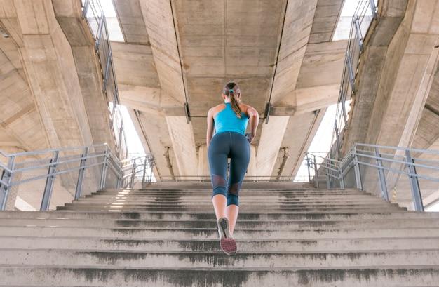 Hintere ansicht der jungen frau in der sportkleidung, die auf treppenhaus rüttelt Kostenlose Fotos