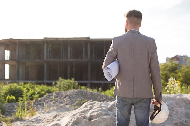 Hintere ansicht der männlichen architektur den plan und schutzhelm halten, die baustelle betrachten Kostenlose Fotos