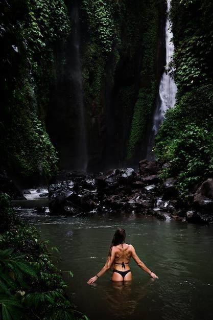 Hintere ansicht der schönheit badend und im natürlichen swimmingpool vor wasserfall im naturpark auf tropeninsel entspannend. schöner wasserfall im bali, indinesien Premium Fotos