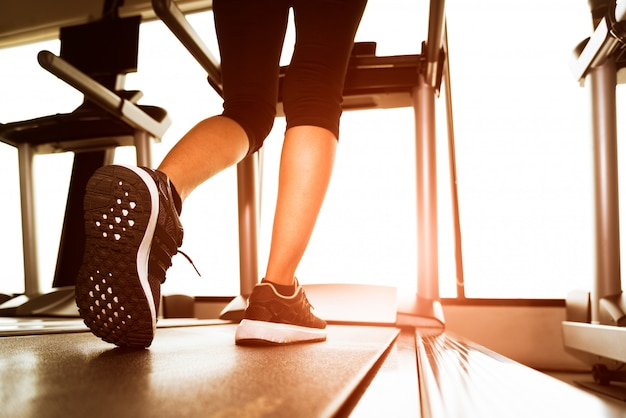 Hintere ansicht der unteren körperbeine des eignungsmädchens laufend auf maschine oder tretmühle in eignung gy Premium Fotos