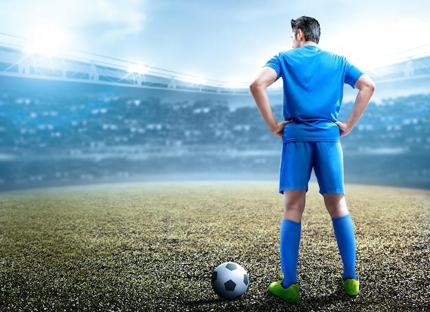 Hintere ansicht des asiatischen fußballspielermannes, der mit dem ball steht Premium Fotos