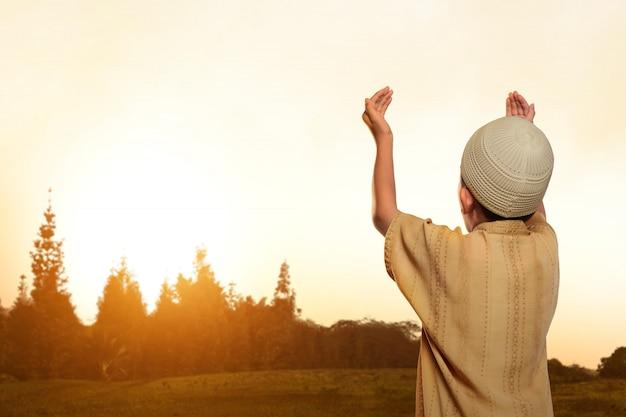 Hintere ansicht des asiatischen moslemischen kindes mit kappe betend zum gott Premium Fotos