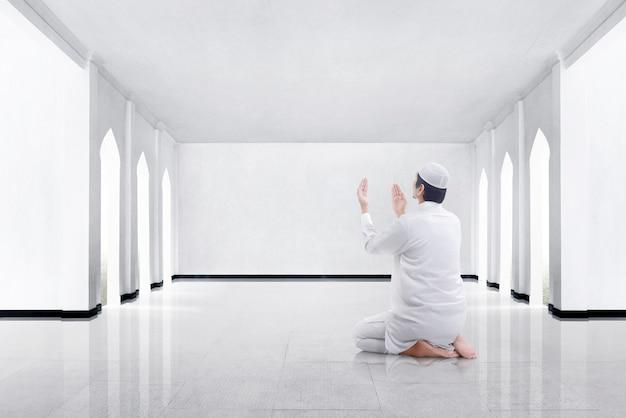 Hintere ansicht des asiatischen moslemischen mannes kniend und zum gott betend Premium Fotos