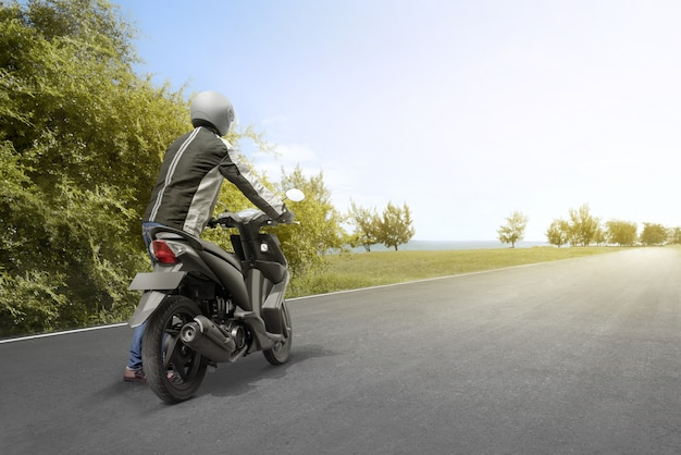 Hintere ansicht des asiatischen motorradtaximannes drückt sein motorrad Premium Fotos