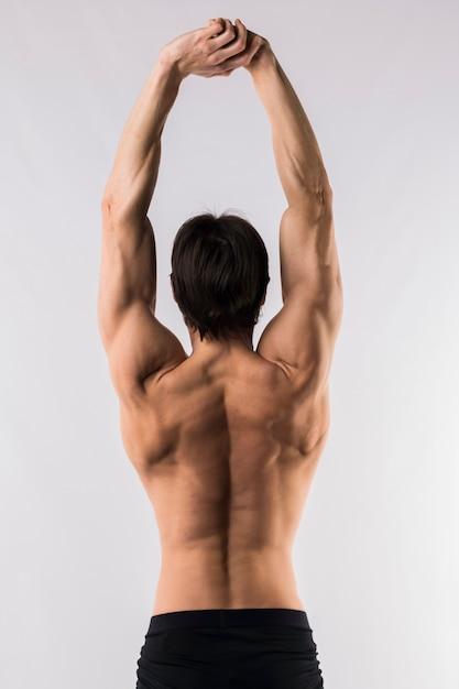 Hintere ansicht des hemdlosen mannes mit muskeln mit den armen oben Kostenlose Fotos