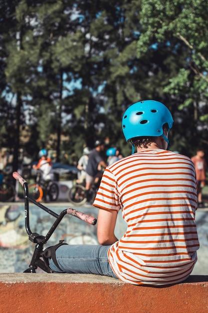 Hintere ansicht des jungen blauen sturzhelm mit dem fahrrad tragend, das draußen sitzt Kostenlose Fotos