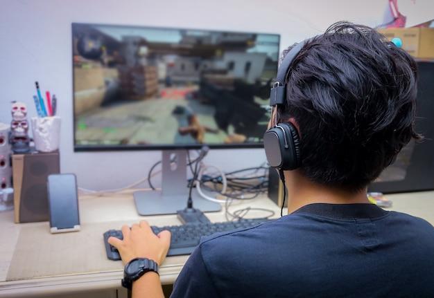 Hintere ansicht des jungen gamers, der fps-videospiele spielt Premium Fotos