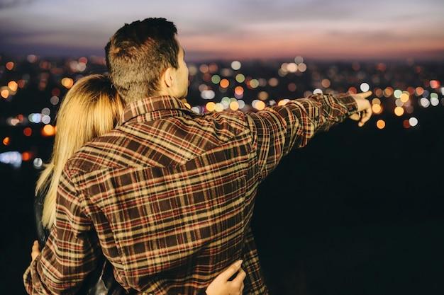 Hintere ansicht des jungen kerls im karierten hemd, das freundin umarmt und auf entfernung zeigt, während auf unscharfem hintergrund der nachtstadt steht Premium Fotos