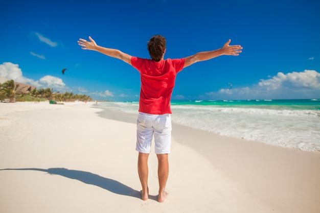 Hintere ansicht des jungen mannes breitete seine hände auf tropischem strand aus Premium Fotos