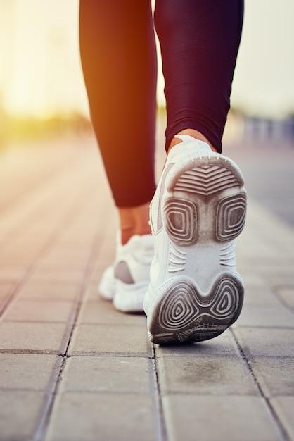 Hintere ansicht des läufers in den sportturnschuhen, die draußen laufen Premium Fotos
