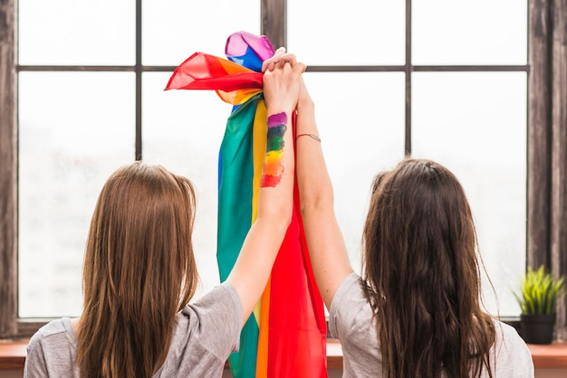 Hintere ansicht des lesbischen jungen paarhändchenhaltens und der regenbogenflagge, die fenster betrachtet Kostenlose Fotos