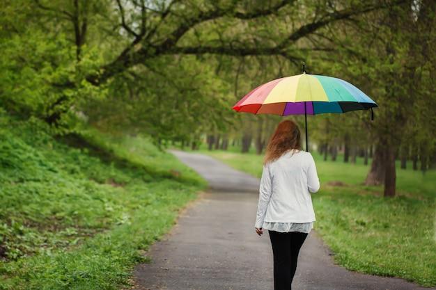 Hintere ansicht des mädchens unter einem hellen regenschirm, gehend in regen Premium Fotos
