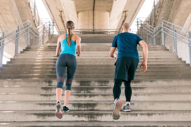Hintere ansicht des männlichen und weiblichen athleten, der auf dem treppenhaus rüttelt Kostenlose Fotos