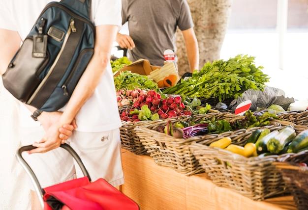 Hintere ansicht des mannes organisches gemüse am markt kaufend Kostenlose Fotos