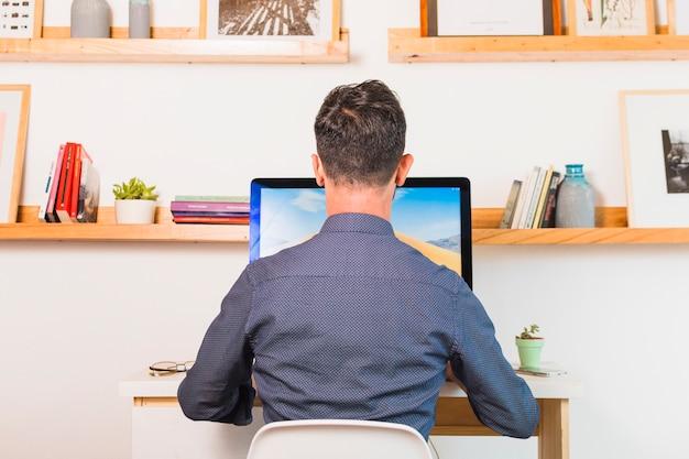Hintere ansicht des mannes sitzend auf stuhl unter verwendung des computers im büro Kostenlose Fotos