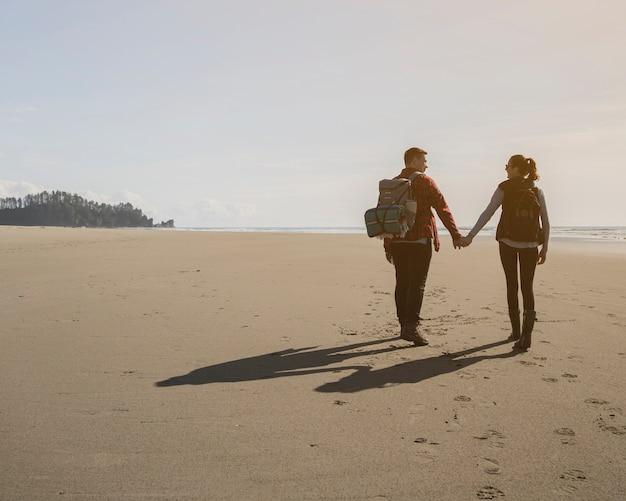 Hintere ansicht des paarhändchenhaltens auf strand Kostenlose Fotos