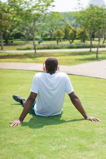 Hintere ansicht des schwarzen mannes stillstehend auf gras mit drahtlosen kopfhörern. Kostenlose Fotos