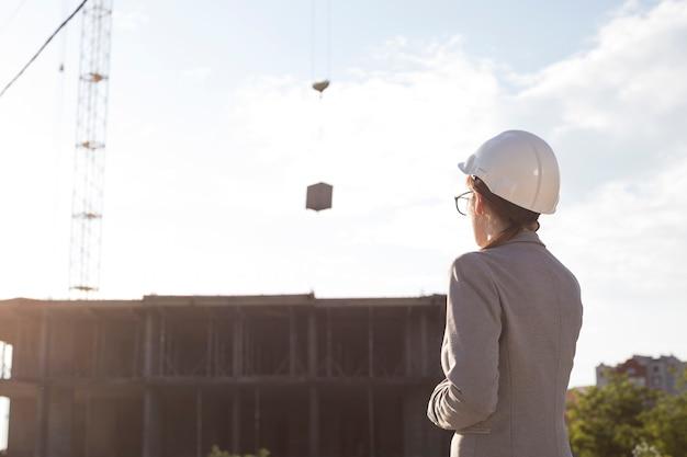 Hintere ansicht des tragenden hirschhutes des weiblichen architekten, der baustelle betrachtet Kostenlose Fotos