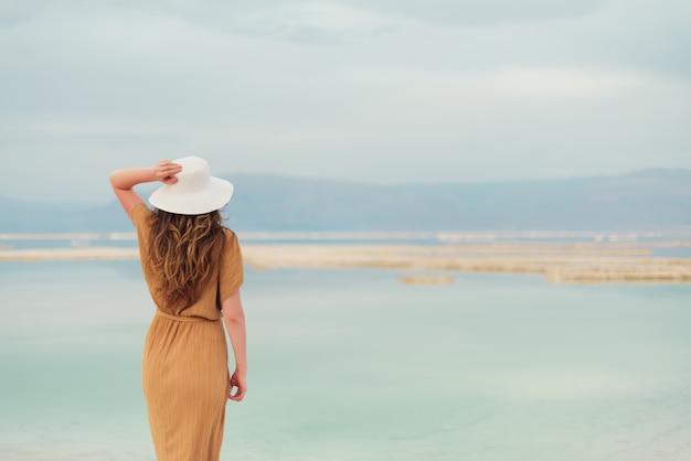 Hintere ansicht des tragenden kleides des stilvollen mädchens auf küste Premium Fotos