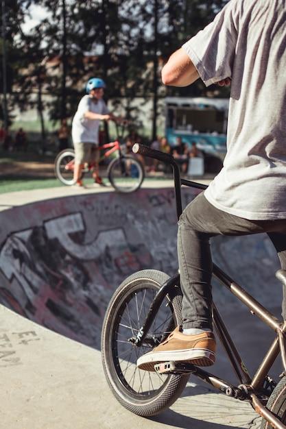 Hintere ansicht des übenden radfahrens des jungen in rochenpark Kostenlose Fotos