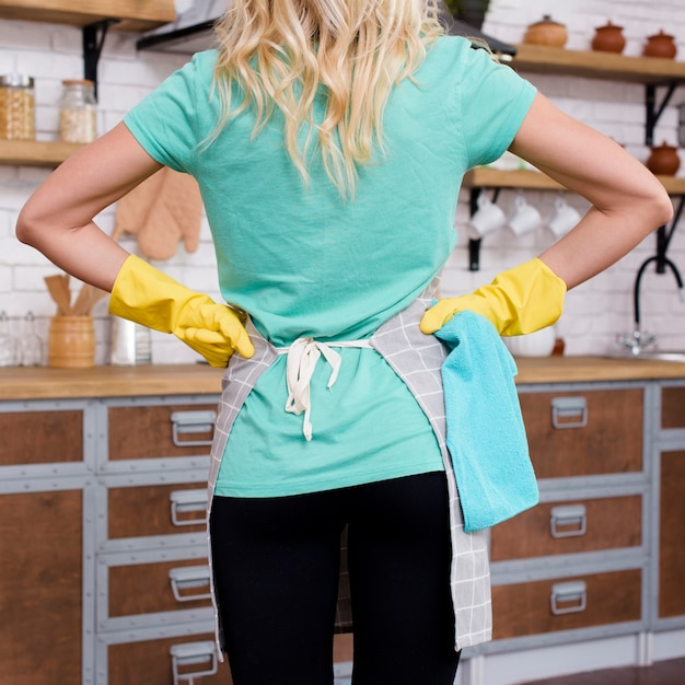 Hintere ansicht einer frau, die in der küche mit den händen auf tragenden gummihandschuhen der taille steht Kostenlose Fotos