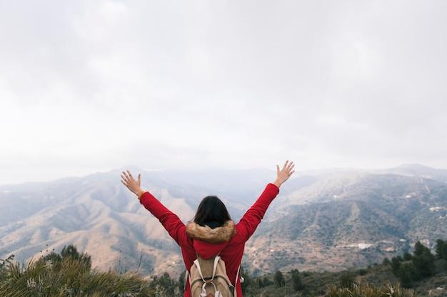 Hintere ansicht einer frau mit dem rucksack, der ihre arme übersehen an der berglandschaft anhebt Kostenlose Fotos