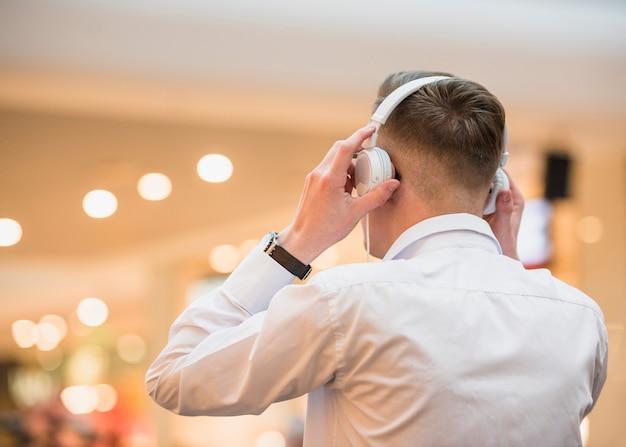 Hintere ansicht einer hörenden musik des jungen mannes auf weißem kopfhörer Kostenlose Fotos