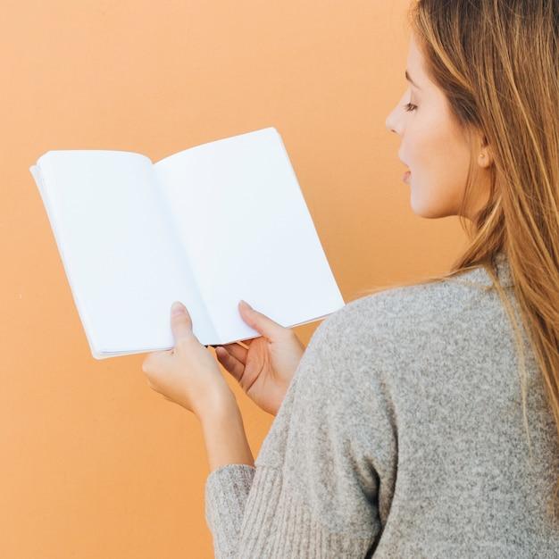 Hintere ansicht einer jungen frau, die in der hand weißbuch gegen pfirsichhintergrund hält Kostenlose Fotos