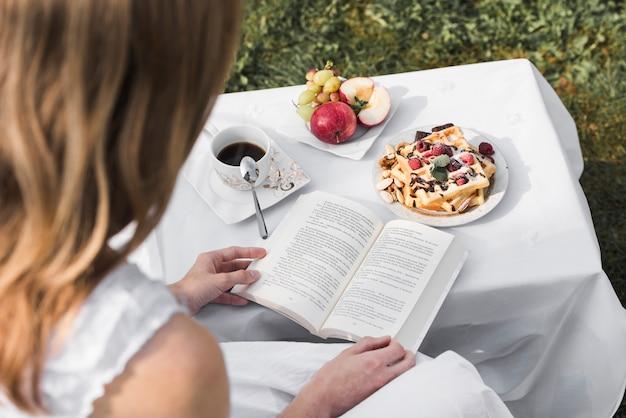 Hintere ansicht eines frauenlesebuches mit gesundem frühstück des morgens auf tabelle an draußen Kostenlose Fotos