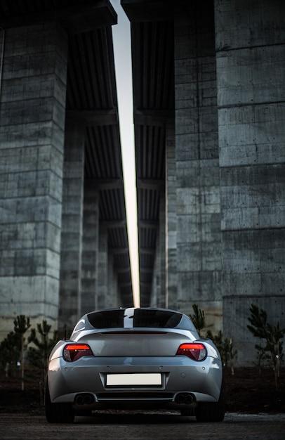 Hintere ansicht eines grauen autos, das unter der brücke steht. Kostenlose Fotos
