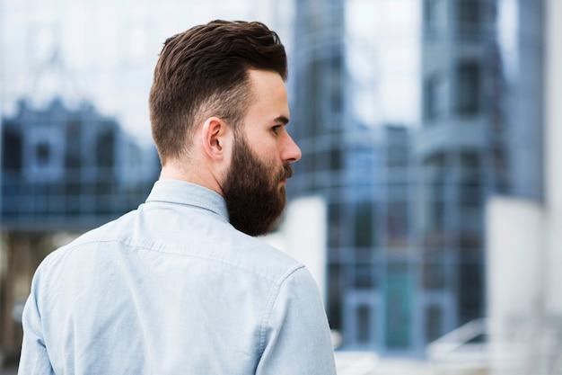 Hintere ansicht eines jungen geschäftsmannes, der über seiner schulter schaut Kostenlose Fotos