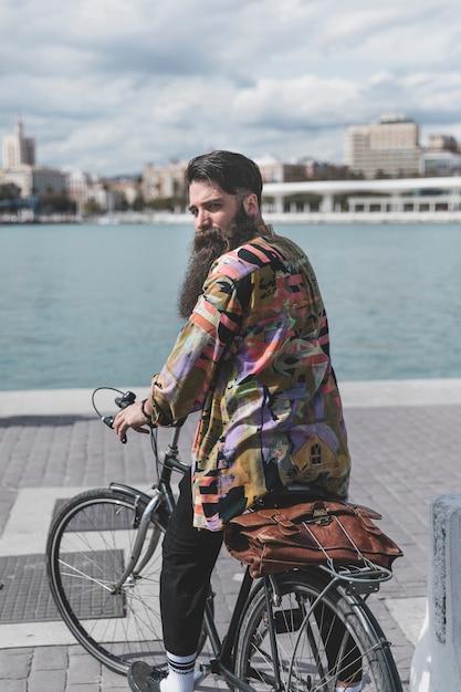 Hintere ansicht eines jungen mannes, der auf dem fahrrad schaut über schulter nahe der küste sitzt Kostenlose Fotos
