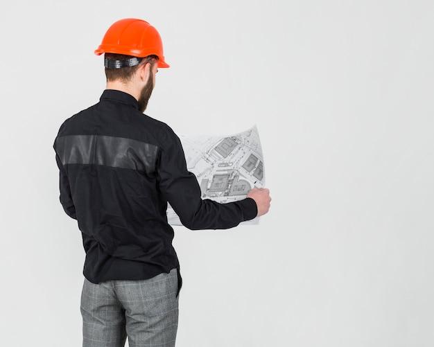 Hintere ansicht eines männlichen architekten, der plan über dem weißen hintergrund betrachtet Kostenlose Fotos