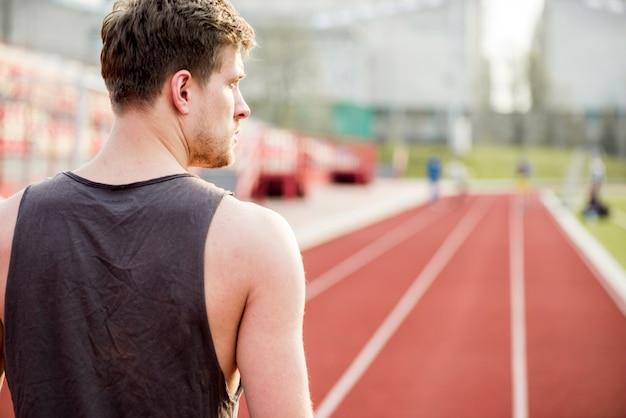 Hintere ansicht eines männlichen läufers, der auf der rennstrecke weg schaut steht Kostenlose Fotos
