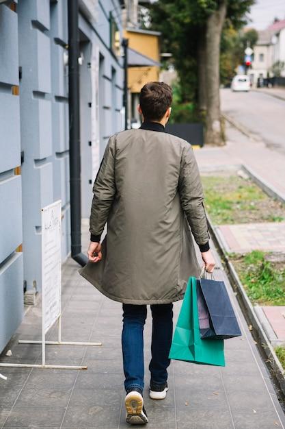 Hintere ansicht eines mannes, der auf den bürgersteig hält einkaufstaschen geht Kostenlose Fotos