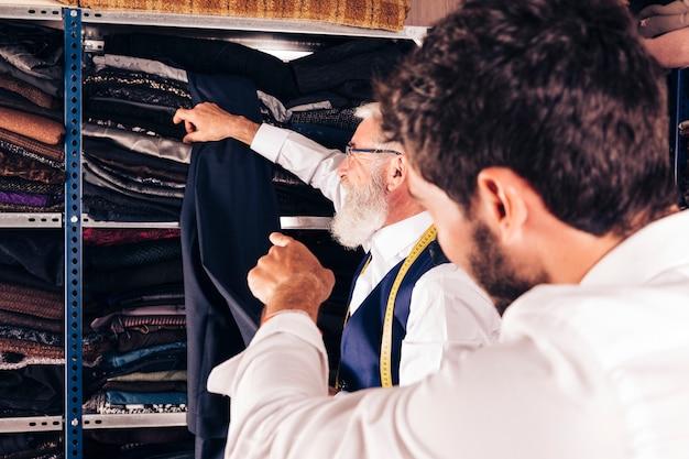 Hintere ansicht eines mannes, der finger auf den älteren modedesigner nimmt gewebe vom regal zeigt Kostenlose Fotos