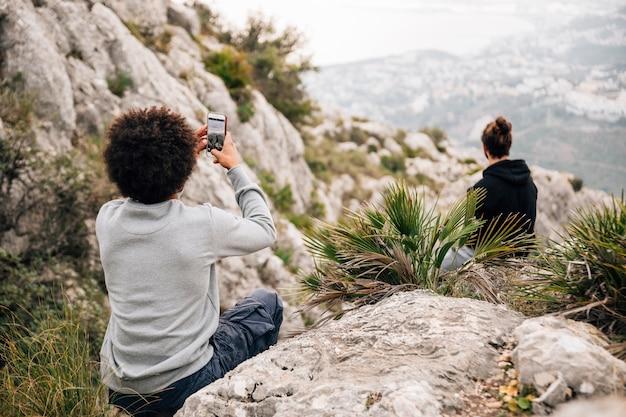 Hintere ansicht eines mannes, der foto seines freundes sitzt auf felsen mit handy macht Kostenlose Fotos