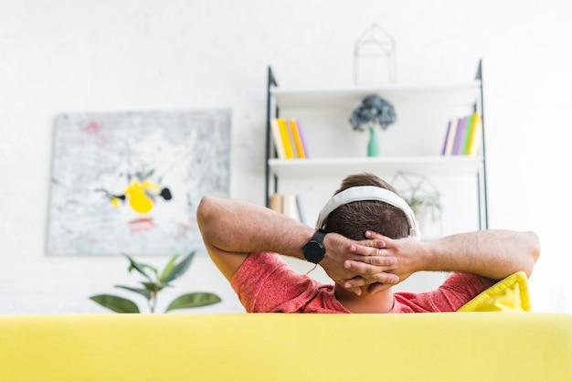 Hintere ansicht eines mannes, der musik auf kopfhörer hört Kostenlose Fotos