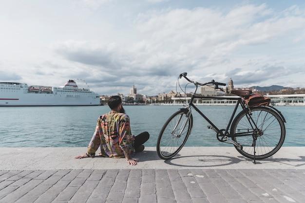Hintere ansicht eines mannes mit dem fahrrad, das nahe bucht sitzt Kostenlose Fotos