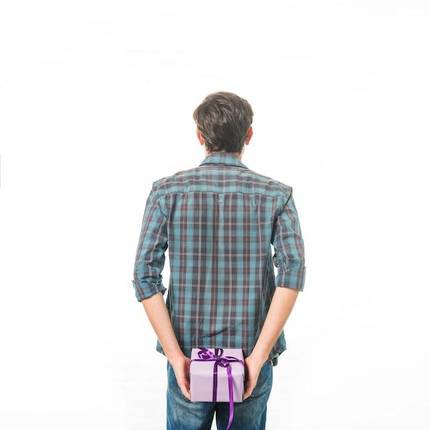 Hintere ansicht eines mannes mit der geschenkbox, die auf weißem hintergrund steht Kostenlose Fotos