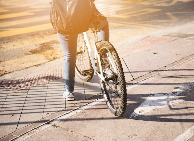 Hintere ansicht eines radfahrers mit dem rucksack, der auf straße wartet Kostenlose Fotos